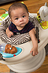 "6 month old baby boy closeup in stationary ""walker"" looking up expression uncertain, concerned"