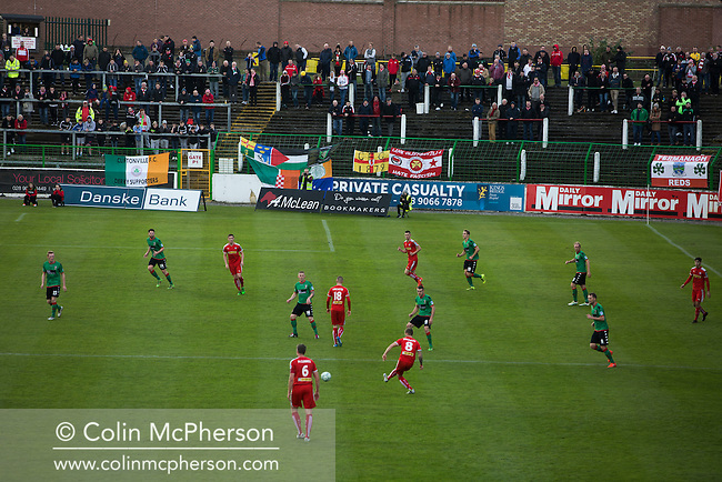 Away supporters watching the first-half action at The Oval, Belfast as Glentoran (in green) host city-rivals Cliftonville in an NIFL Premiership match. Glentoran, formed in 1892, have been based at The Oval since their formation and are historically one of Northern Ireland's 'big two' football clubs. They had an unprecendentally bad start to the 2016-17 league campaign, but came from behind to win this fixture 2-1, watched by a crowd of 1872.