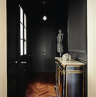 A dramatic black palette is the backdrop to an antique gilded sideboard. A Stockman mannequin designed by artist Emmanuel Bossuet stands in one corner.