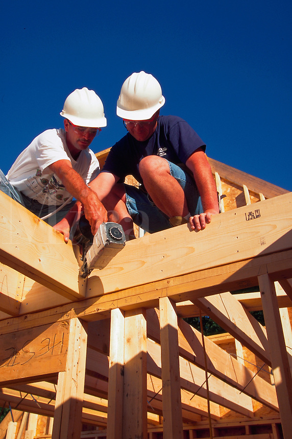 Two men in hardhats building the frame of a house.