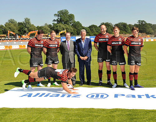 24.7.2012. Barnet, England. Schalk Brits of Saracens shows how tries will be scored on a artificial turf which Sarries will play on. Clement B. Booth, Member of the Board of Management, Allianz Group with Saracens Chairman Nigel Wray and Saracens players in there new kit for the season at Saracens press conference. Saracens have announced a groundbreaking £9m sponsorship deal with Allianz that will see the insurance giant take naming rights for the rugby club's new home in north London which will be known as Allianz Park at Barnet Copthall Stadium on 24 July 2012.