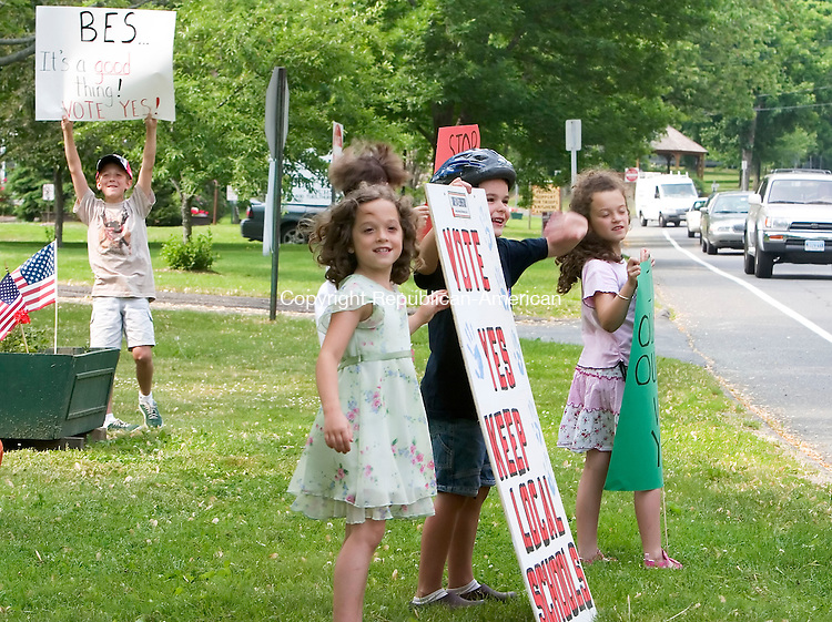 BETHLEHEM, CT- 31 MAY 2007- 053107JT01- <br /> <br /> From left to right, Nick DeCicco, 9, Megan DeCicco, 7, Claire Scherf (partially obscured), 8, Leo Scherf, 6, and Taylor DeCicco, 7, wave to a school bus that honked at them as they display signs in front of Bethlehem Town Hall on Thursday as voters entered the polling station to decide on an amendment proposed by the Save Region 14 Elementary group to amend the 1968 school regionalization plan. If the schools are reconfigured, Nick DeCicco and his twin sisters would attend separate schools, as would siblings Leo and Claire Scherf.<br /> Josalee Thrift Republican-American