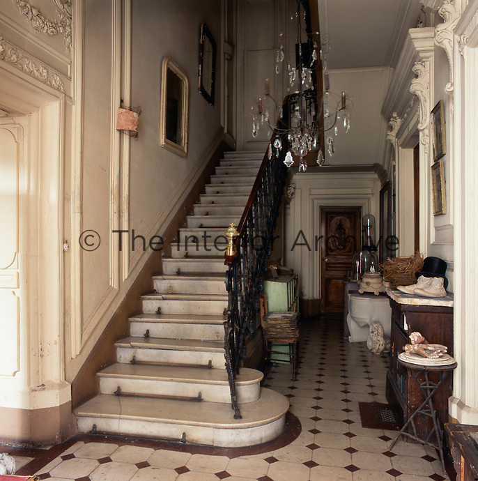 An elegant entrance hallway with a grand marble staircase and ornate plasterwork above the doorways.