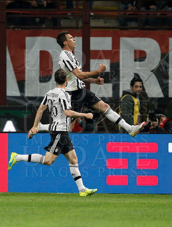 Calcio, Serie A: Milan vs Juventus. Milano, stadio San Siro, 9 aprile 2016. <br /> Juventus&rsquo; Mario Mandzukic, top, celebrates with teammate Stephan Lichsteiner after scoring during the Italian Serie A football match between AC Milan and Juventus at Milan's San Siro stadium, 9 April 2016.<br /> UPDATE IMAGES PRESS/Isabella Bonotto