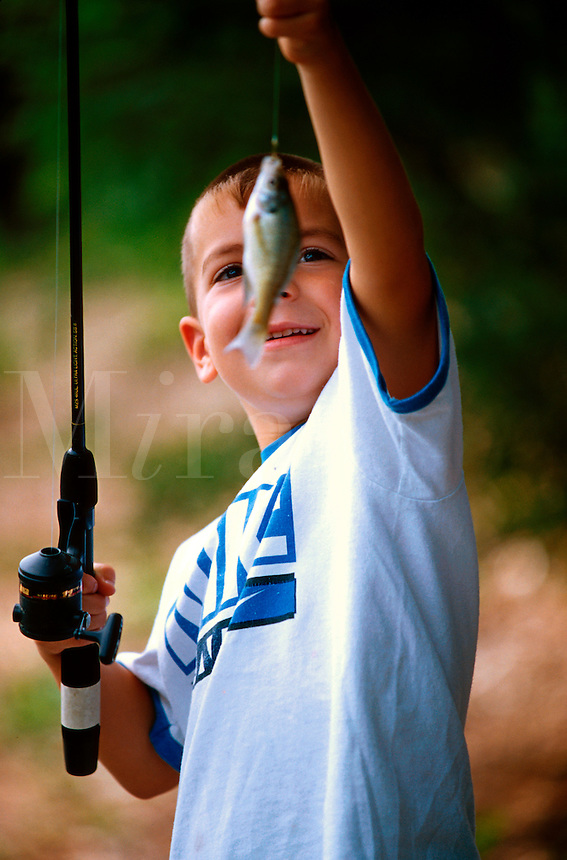 A smiling young boy admires the small fish he has caught with his fishing pole.