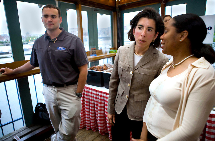 Small business owner, Aaron Atwood, left, waits to speak with RI General Treasurer Candidate Gina Raimondo, center, during a campaign kickoff fundraising event in Providence, on Tuesday night, at The Hot Club.