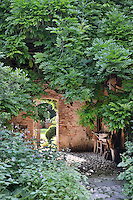 The corner of a garden space surrounded by foliage. An arched opening in a stone wall leads to a further garden area beyond.