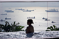 Singapore. Marina Bay Sands Hotel. Ships waiting to enter the harbor, seen from the whirlpool next to the infinity pool at the rooftop.