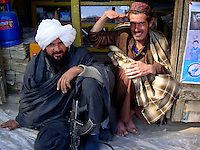 A commander and foot sioldier from the Wardak Mobile Patrol Unit relax in comfort in a village armed with an AK47 machine gun