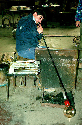 Murano, Italy - March 25, 2006 -- An unidentified artesian blows glass to be used to make a bowl at a factory in Murano, Italy on March 25, 2006..Credit: Ron Sachs / CNP