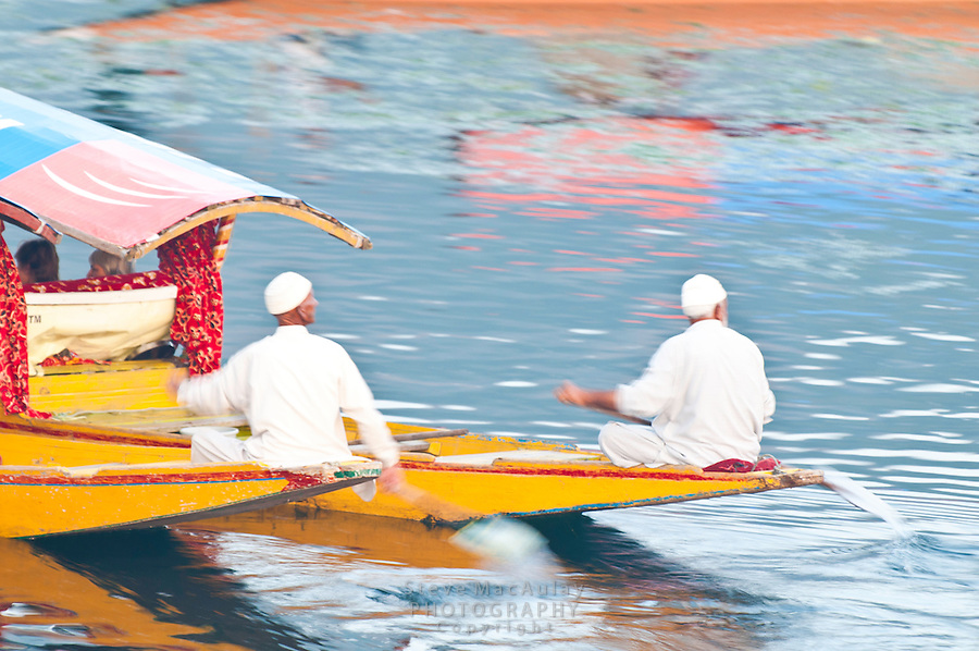 Graphic motion photograph of a pair of men paddling traditional Kashmiri shikaras, or gondolas, Dal Lake, Srinagar, Kashmir, india.
