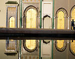 Man standing by pool, reflection of building in water, Dar el-Makhzen