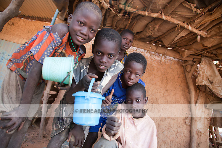 Quranic students roam the market in Djibo, northern Burkina Faso.  It is tradition for these religious students to beg for their meals.  Diners in the market place leftovers in plastic pails carried by the children.