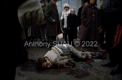 Bucharest, Romania<br /> December 1989<br /> <br /> Romanians look down with hatred at the corpse of a suspected Securitate member - former leader Nicolae Ceausescu's secret police.<br /> <br /> The week-long series of violence that overthrew the Communist regime of Nicolae Ceausescu, ended in a trial and execution of Ceausescu and his wife Elena by firing squad. Romania was the only Eastern Bloc country to violently overthrow its Communist regime or to execute its leaders.<br /> <br /> The Romanian populace was dissatisfied with the Communist regime and leader Ceausescu's economic and development policies were blamed for the country's shortages and widespread poverty. The powerful secret police (Securitate) controlled what was essentially a police state. Ceausescu was not pro-Soviet but &quot;independent&quot; on foreign policy. He imitated the hard-line, megalomania, and personality cults of communist leaders like North Korea's Kim Il Sung.