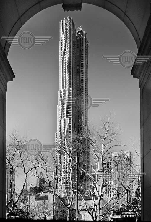 The Gehry Tower, a residential skyscraper designed by Frank Gehry, in downtown Manhattan, as seen from the arches of municipal building.