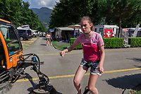 Switzerland. Canton Ticino. Tenero. Camping Campofelice. Garbage collectors. Streets cleaning. A street sweeper drives a street brooming machine on the road. The worker and his machine pass near a teenage girl riding a one-wheeled unicycle driven by pedals. A swiss flag is laid on a caravan. A campervan (or camper van), sometimes referred to as a camper, or a caravanette, is a self-propelled vehicle that provides both transport and sleeping accommodation. A motorhome (or motor coach is a type of self-propelled recreational vehicle (RV) which offers living accommodation combined with a vehicle engine. Motorhomes are part of the much larger associated group of mobile homes which includes caravans, also known as tourers, and static caravans. A caravan, travel trailer, camper or camper trailer is towed behind a road vehicle to provide a place to sleep which is more comfortable and protected than a tent. It provides the means for people to have their own home on a journey or a vacation. Campers are restricted to designated sites for which fees are payable. The flag of Switzerland consists of a red flag with a white cross (a bold, equilateral cross) in the centre. It is one of only two square sovereign-state flags. 20.07.2018 © 2018 Didier Ruef