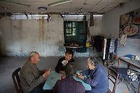Patients and their relatives play cards at a dilapidated service building of Yangjia Hospital in Wuji County, China's Zhejiang Province October 19, 2015. Yangjia Hospital, once considered top medical institution treating pneumoconiosis with latest imported equipment is not able to keep the high standards since becoming private in 2001 and is now offering only basic care for remaining patients, all of them former miners suffering from diseases causes by dust in lungs. Patients are often accompanied by their relatives who cook their own food at the hospital.     REUTERS/Damir Sagolj