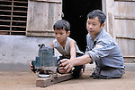 Tran Van Son is a carpenter in Bo Trach, Vietnam, who lost his legs to a landmine from the U.S. war against Vietnam. Here he helps his son Tran Xuan Lam learn the trade.