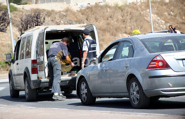 Israeli police inspect a car at a checkpoint in Jerusalem's Old city on October 14, 2015. Seven Israelis and 30 Palestinians, including children and assailants, have been killed in two weeks of bloodshed in Israel, Jerusalem and the occupied West Bank. The violence has been partly triggered by Palestinians' anger over what they see as increased Jewish encroachment on Jerusalem's Al-Aqsa mosque compound. Photo by Mahfouz Abu Turk