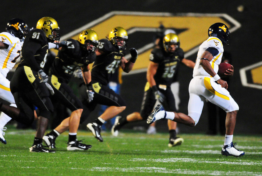 18 September 08: West Virginia quarterback Pat White runs to avoid Colorado defenders, from left, Maurice Lucas, Shaun Mohler, Jeff Smart, and Ryan Walters. The Colorado Buffaloes defeated the West Virginia Mountaineers 17-14 in overtime at Folsom Field in Boulder, Colorado. For Editorial Use Only.