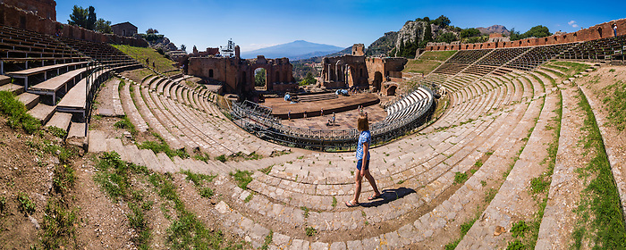 Teatro Greco aka Taormina Greek Theatre, panoramic photo of tourist sightseeing at the amphitheatre with Mount Etna Volcano behind, Sicily, Italy, Europe. This is a panoramic photo of a tourist sightseeing at Teatro Greco aka Taormina Greek Theatre or Amphitheatre, with Mount Etna Volcano in the background, Sicily, Italy, Europe. When sightseeing, this is one the best things to do as a tourist in Taormina thanks to its stunning location with panoramic views of Mount Etna.