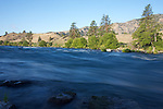 The blue sky of morning reflects in the shadowed water of the Deschutes River, Oregon.