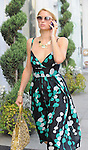 OCTOBER 29TH 2010 ..Paris Hilton walking down Santa Monica Blvd while talking on her cell phone filming a movie in Los Angels. Paris was wearing a green & black & white polka dot circle dress. & carrying a big funky looking gold yellow purse handbag & an owl necklace. ..ABILITYFILMS@YAHOO.COM.805-427-3519.WWW.ABILITYFILMS.COM.