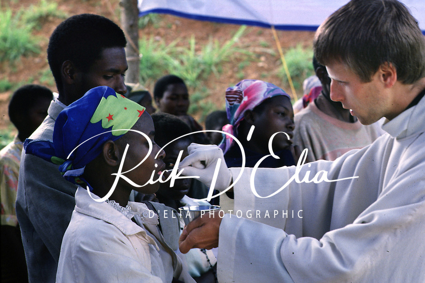 Father Philippe Marie Meuret of the Fraternite de Norte Dame oreder gives communion to a Rwandan woman in a makeshift chapel on the compound the AmeriCares clinic in Buranga, Rwanda, October 1994. The New Canaan Connecticut humanitarian organization set up their clinic on the road between Goma, Zaire (now Congo) and Kigali, Rwanda to help refugees returning from the camps in Goma and the people living in the area whose illnesses resulted from the destruction of what little infrastructure existed before civil war. (photo Rick D'Elia)
