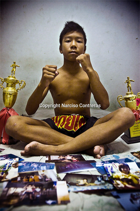 Keng is posing with some of the trophies had won at his bedroom. Keng is a 12 years old kid, and he has fighted over 70 times, he has been champion in Chiang Mai, and is reconized in several boxing circles around the city. His father passed away when he was 7 years old, and now help his mother earning half of  the income that she is getting per month each time he fight. For them there is not other way. He is going by the hand of his mother to each combat. Shy and reserved is holding his dream to reach the big Bangkok  competitions in future.