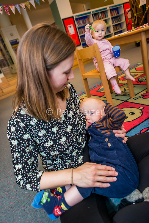 A young woman breastfeeds one of her twins while sitting on the floor of a public library. Her other twin sits on a chair in the background.<br /> <br /> 24/11/12<br /> Hampshire, England, UK