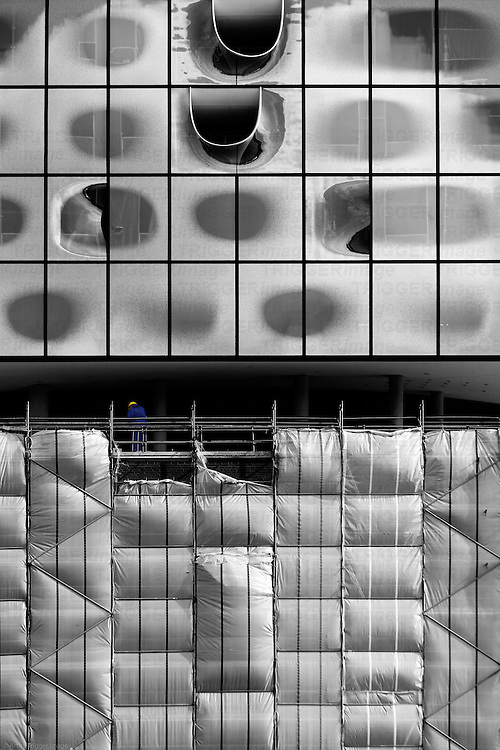A worker at a floor of the Elbe Philharmonic Hall in Hamburg between the finished facade and scaffolding.