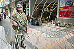 Apr. 19 2010 - BANGKOK, THAILAND: A Thai soldier on duty behind a wall of razor wire in the Silom financial district in Bangkok Monday. Hundreds of Thai soldiers, including reservists and front line units, and riot police moved into the Silom financial district Monday, not far from the red-shirts' main protest rally site, in Ratchaprasong. The heavy show of force is to prevent the Red Shirts from entering the Silom area. Many of soldiers were greeted as heros by workers in the area, who oppose the Red Shirts.   Photo by Jack Kurtz