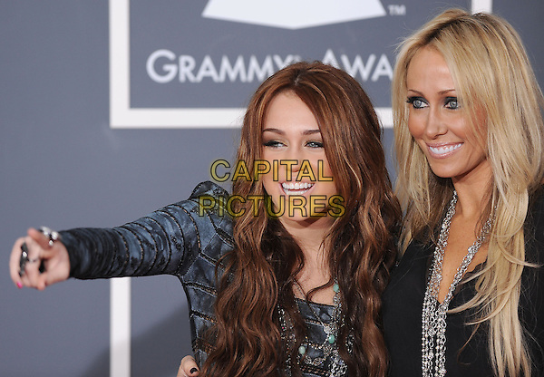 MILEY CYRUS & TISH CYRUS.Arrivals at the 52nd Annual GRAMMY Awards held at The Staples Center in Los Angeles, California, USA..January 31st, 2010.grammys half length grey gray blue pattern dress long sleeves black top daughter mother mom mum silver necklace hand arm pointing .CAP/RKE/DVS.©DVS/RockinExposures/Capital Pictures