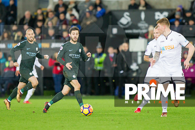 Bernardo Silva of Manchester City passes wide of Alfie Mawson of Swansea City during the EPL - Premier League match between Swansea City and Manchester City at the Liberty Stadium, Swansea, Wales on 13 December 2017. Photo by Mark  Hawkins / PRiME Media Images.