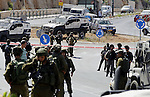 Israeli security forces gather at the scene where a female Palestinian was shot dead by Israeli troops at the entrance to Kiryat Arba near the West Bank city of Hebron June 24, 2016. Photo by Wisam Hashlamoun