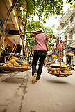 VIETNAM, Hanoi, a street scene of a woman walking down the street selling pineapples