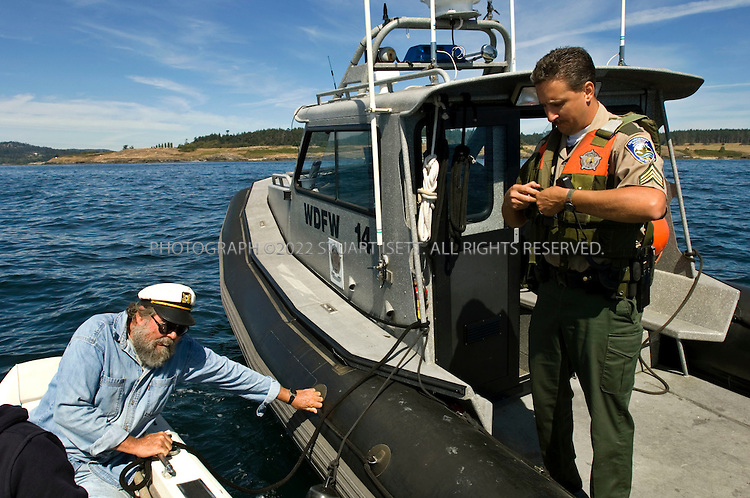 """8/28/2006--San Juan Island, WA, USA...Kenneth Balcomb, 65, of the Center for Whale Research, talks with officers from the Washington State Department of Fish and Wildlife off the shores of the San Juan Island. Balcomb started the Orca Survey in 1976 and has been the Executive Director and Research Biologist for the Center for Whale Research since 1985...The federal govt is talking about dramatic protection for endangered killer whales in Puget Sound, enraging business interests in a fast-growing region of the Pacific NW. A specific orca population - about 90 orcas who feed exclusively on Puget Sound salmon - was added to the Endangered Species List in 2005. Now the National Marine Fisheries Service wants to designate 2,500 sq miles of inland waters - half of the Strait of Juan de Fuca, waters around the San Juan Islands (playground for Seattle?s rich) and most of Puget Sound - as """"critical habitat"""" worthy of environmental restrictions. Developers and farmers (and a conservative land-rights group) have sued to block the plan, while environmentalists say it doesn't go far enough...Assignment ID: 30028811A.Slug: orca...Photograph By Stuart Isett.All photographs ©2006 Stuart Isett.All rights reserved."""