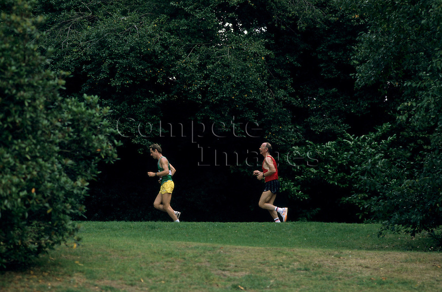 Two men jogging through a wooded area