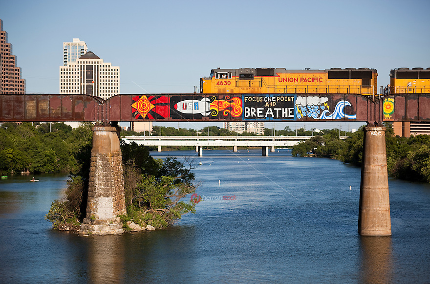 Train with graffiti runs on the Union Pacific Train Tressel Bridge over Lake Austin