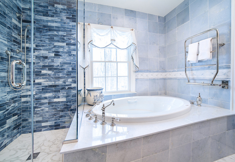 """This custom bathroom features Marabel shown in Thassos and Calacatta on the floor, 3""""x 12"""" Marcasite glass bricks in the shower, and a 6"""" Marabel border in Thassos, Carrara and Celeste as a chair rail.<br /> -photo courtesy of Mediterranean Tile Marble; medtile.com<br /> <br /> For pricing samples and design help, click here: http://www.newravenna.com/showrooms/"""