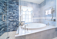 "This custom bathroom features Marabel shown in Thassos and Calacatta on the floor, 3""x 12"" Marcasite glass bricks in the shower, and a 6"" Marabel border in Thassos, Carrara and Celeste as a chair rail.<br />