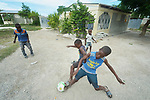 Children play in front of a house built by Servicio Social de las Iglesis Dominicanas in the Haitian community of Ganthier. SSID, a member of the ACT Alliance, has worked extensively in the community since it was devastated in 2016 by Hurricane Matthew.