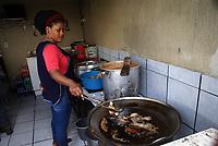 """ACOMPAÑA CRÓNICA: MÉXICO MIGRACIÓN - MEX05. TIJUANA(MÉXICO), 16/06/2017.- Fotografía del 22 de mayo 2017, de una ciudadana haitiana que cocina en el restaurante del mexicano José Luis Bernabé, en Tijuana (México). Para Bernabé la incorporación de jóvenes cocineras haitianas en su restaurante le dio una oportunidad para dar un giro a su negocio. Empezó a recibir a muchos migrantes haitianos a quienes no les convencían los productos que ofrecía: """"Llegó un momento en el que unas chicas haitianas nos pidieron permiso para cocinar y hacer su comida"""", relata.Ahora, el pequeño restaurante de José Luis, en cuya fachada ha pintado una bandera haitiana, se dedica exclusivamente a la comida de ese país, y actualmente da empleo a dos cocineras. EFE/Alejandro Zepeda"""