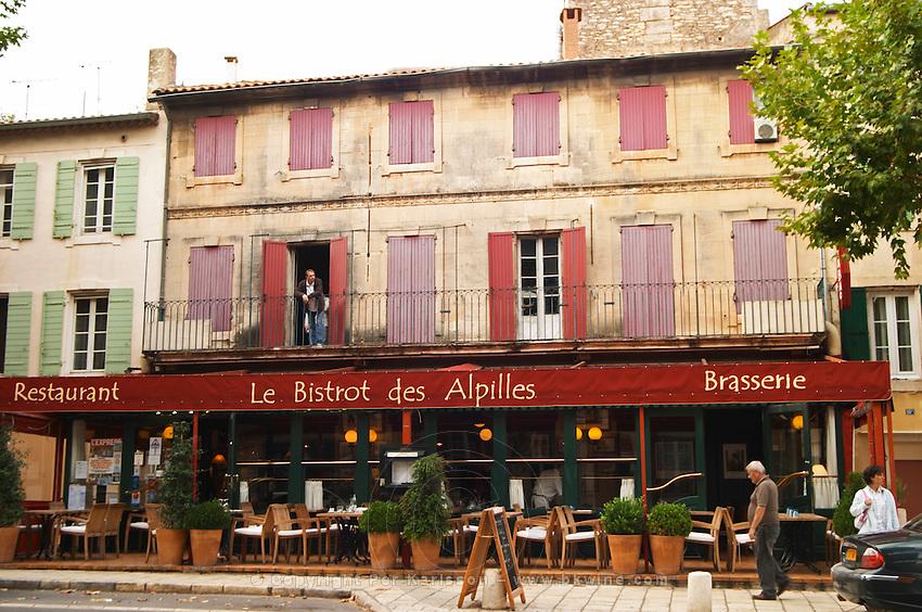 Le Bistrot des Alpilles restaurant. Empty terrace, no person, a man standing on the balcony and a man walking on the pavement sidewalk Saint Remy Rémy de Provence, Bouches du Rhone, France, Europe