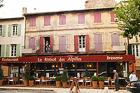 Le Bistrot des Alpilles restaurant. Empty terrace, no person, a man standing on the balcony and a man walking on the pavement sidewalk Saint Remy Rémy de Provence, Bouches du Rhone, France, Europe