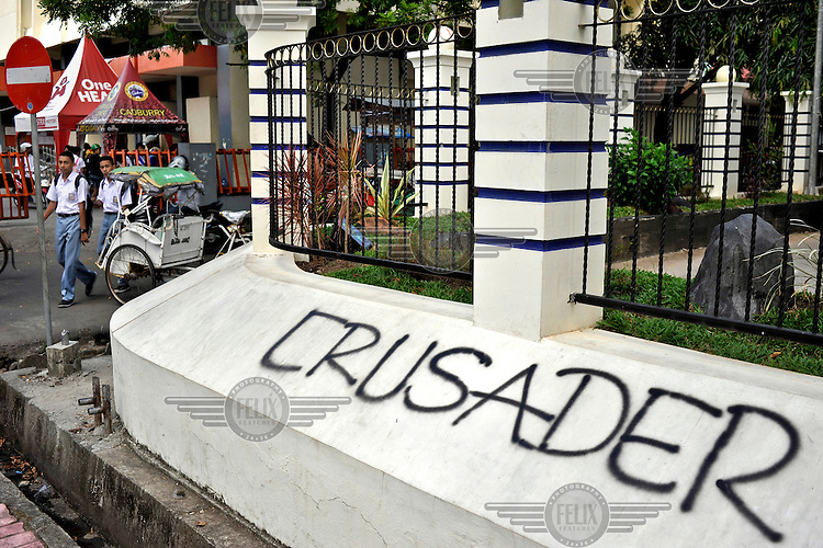 """Graffiti reading """"Crusader"""" (Christian Holy Warrior) in the Christian area of Ambon City near to the main Catholic Cathedral. The 1999-2002 religious war between Maluku's Christian and Muslim populations, mainly centred on Ambon Island, led to over 5000 deaths and to around 500,000 people become displaced. Destroyed homes and offices, churches and mosques are slowly being either torn-down or renovated.  Urban centres, such as Ambon City, continue to be split along largely sectarian lines, and tensions are never far below the surface. Riots between Christian and Muslim youths erupted in September 2011 and, most recently, June 2012, though luckily simmered down just as quickly, partly due to community leaders learning how to defuse tensions from the earlier, more devastating, conflagration. /Felix Features"""