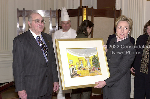 "Washington, DC - December 4, 2000 -- First lady and United States Senator-elect Hillary Rodham Clinton (Democrat of New York), right, holds the original painting of the 2000 White House Christmas card with artist Ray Ellis, left, in the State Dining Room of the White House.  The theme for this year's White House decorations is ""Holiday Reflections"" of past decorations during the Clinton Administration..Credit: Ron Sachs - CNP"