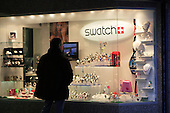 A man is window shopping , looking at Swatch display in store window in downtown Montreal