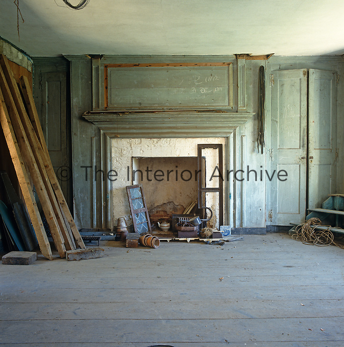 The original paintwork on the panelled walls of this former living room has faded to a variegated bluey green