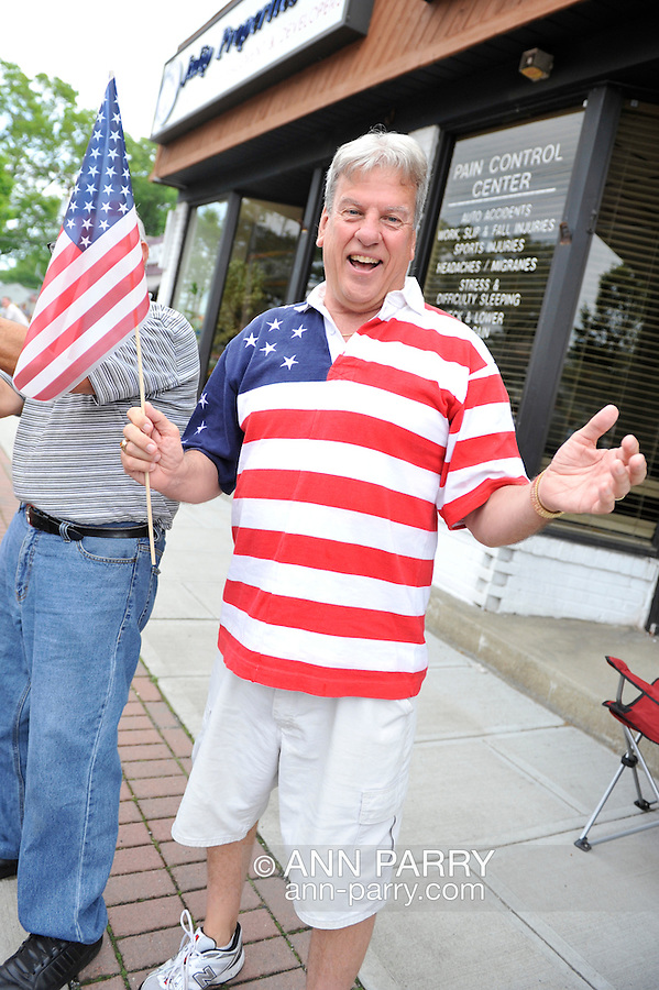 Man wearing shirt with American Flag design watches the Merrick Memorial Day Parade on Monday, May 28, 2012, on Long Island, New York, USA. America's war heroes are honored on this National Holiday.
